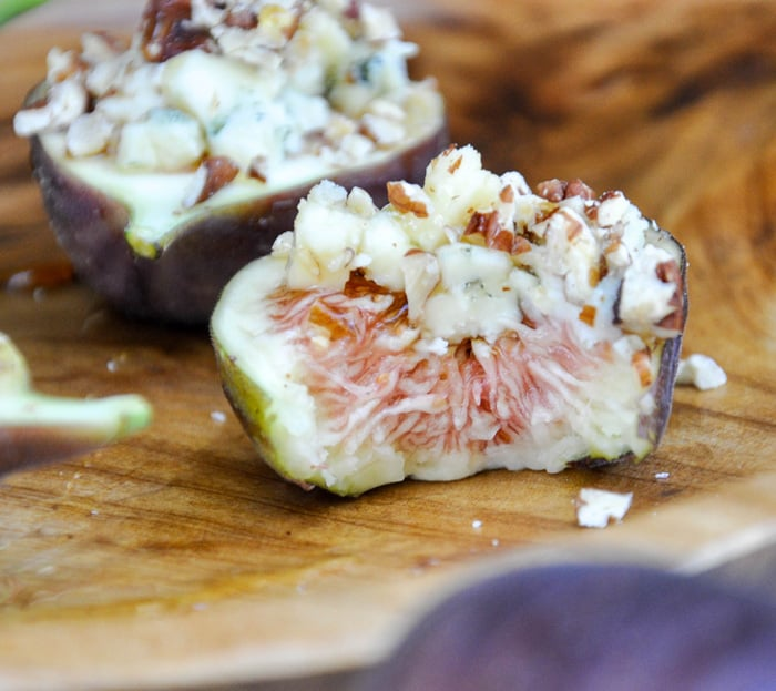 Fresh figs topped with Blue Cheese, Pecans and Honey with a bite taken out of it