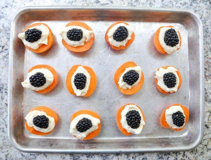 Blackberries top the whipped cream filled apricot