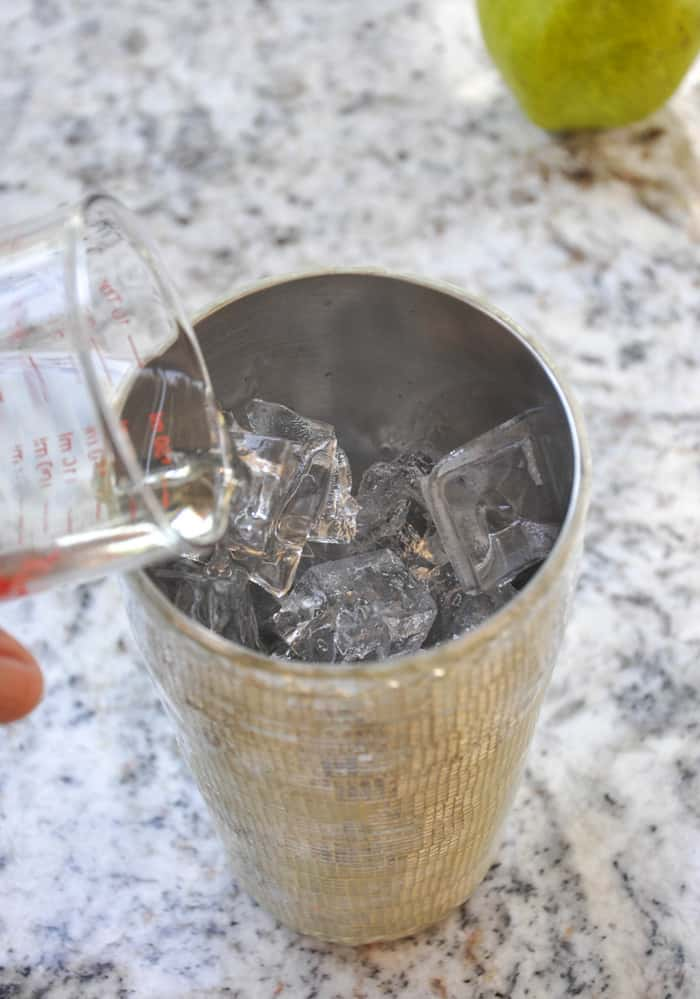 Pouring vodka in cocktail shaker over ice