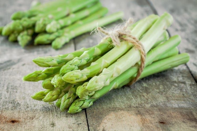 bundle of of ripe organic asparagus on a wooden background