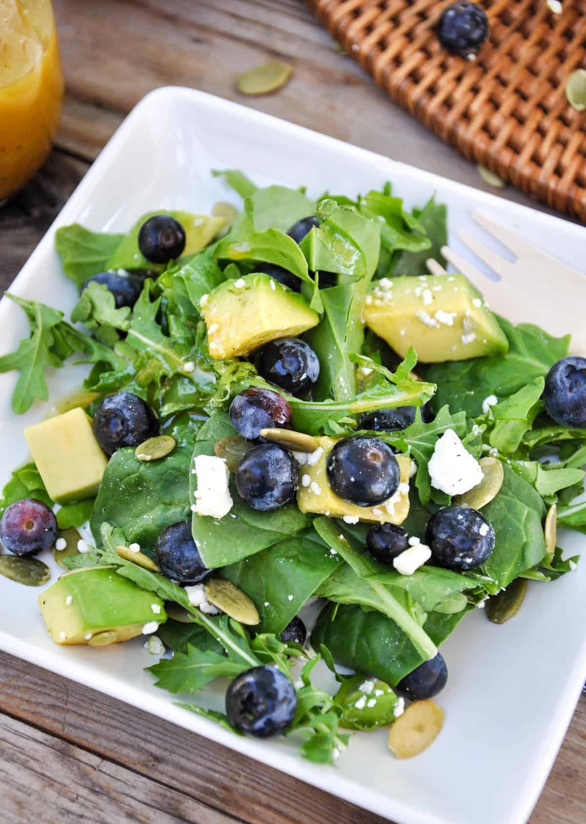 Close up of Blueberry Avocado Salad with feta, pumpkin seeds in a honey vinaigrette