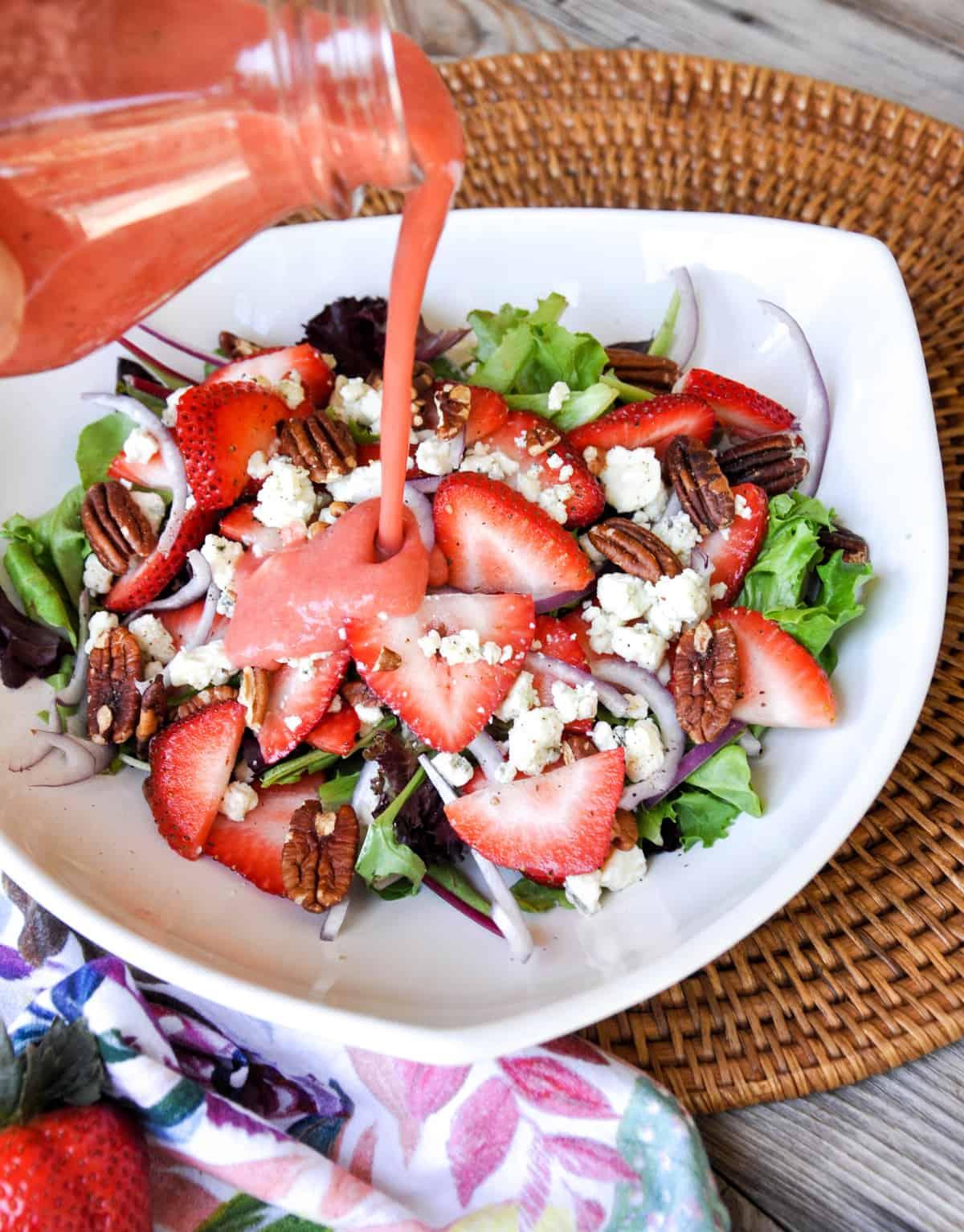 Pouring strawberry vinaigrette on Strawberry Salad