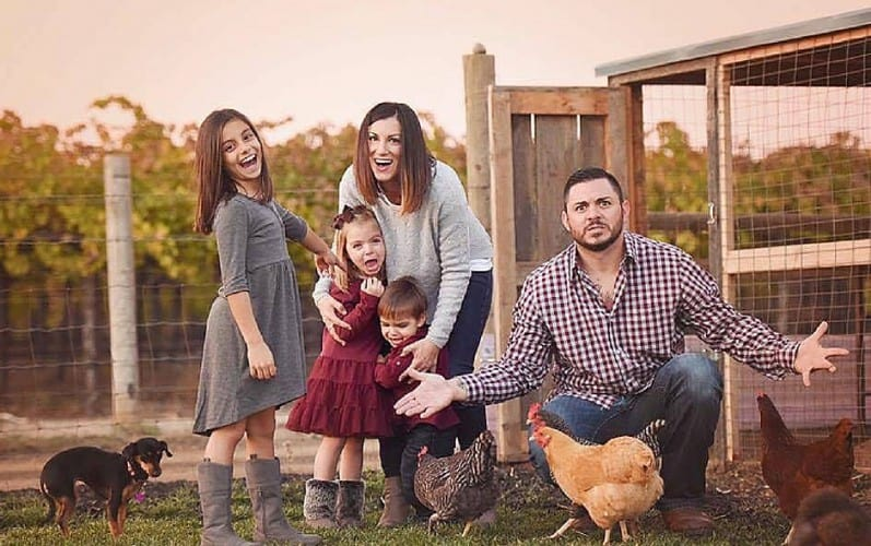 A farmer and his family being silly outside of a chicken coop making faces.