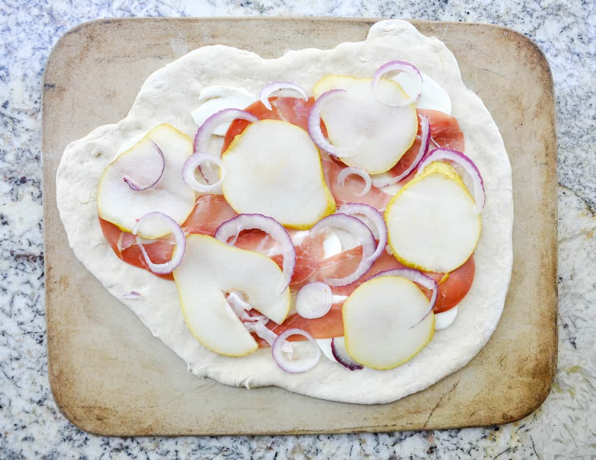 Pear & Prosciutto Pizza topped with red onion and gorgonzola. Yum-O-Licious!