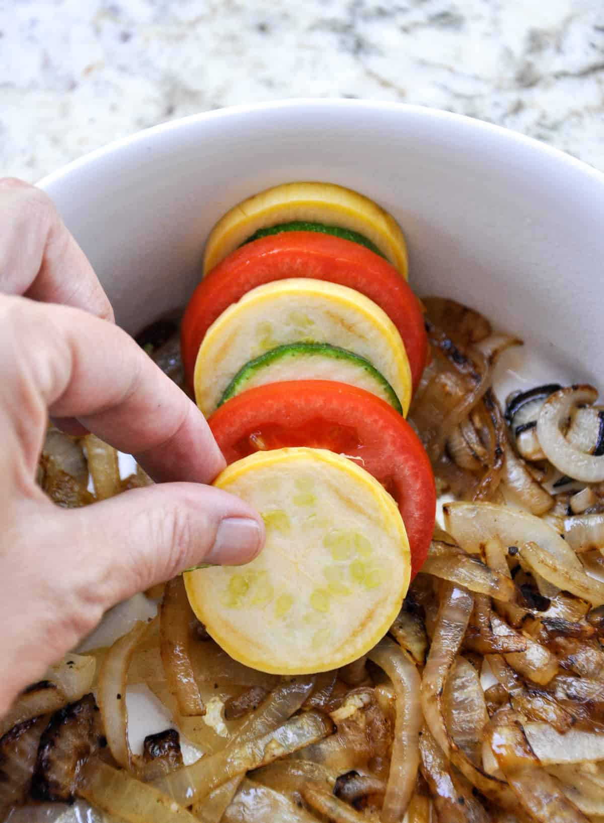 Layer zucchini and tomatoes over caramelized onion bed