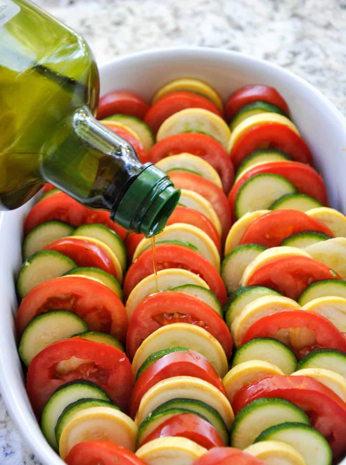Drizzle olive oil over layered zucchini and tomatoes