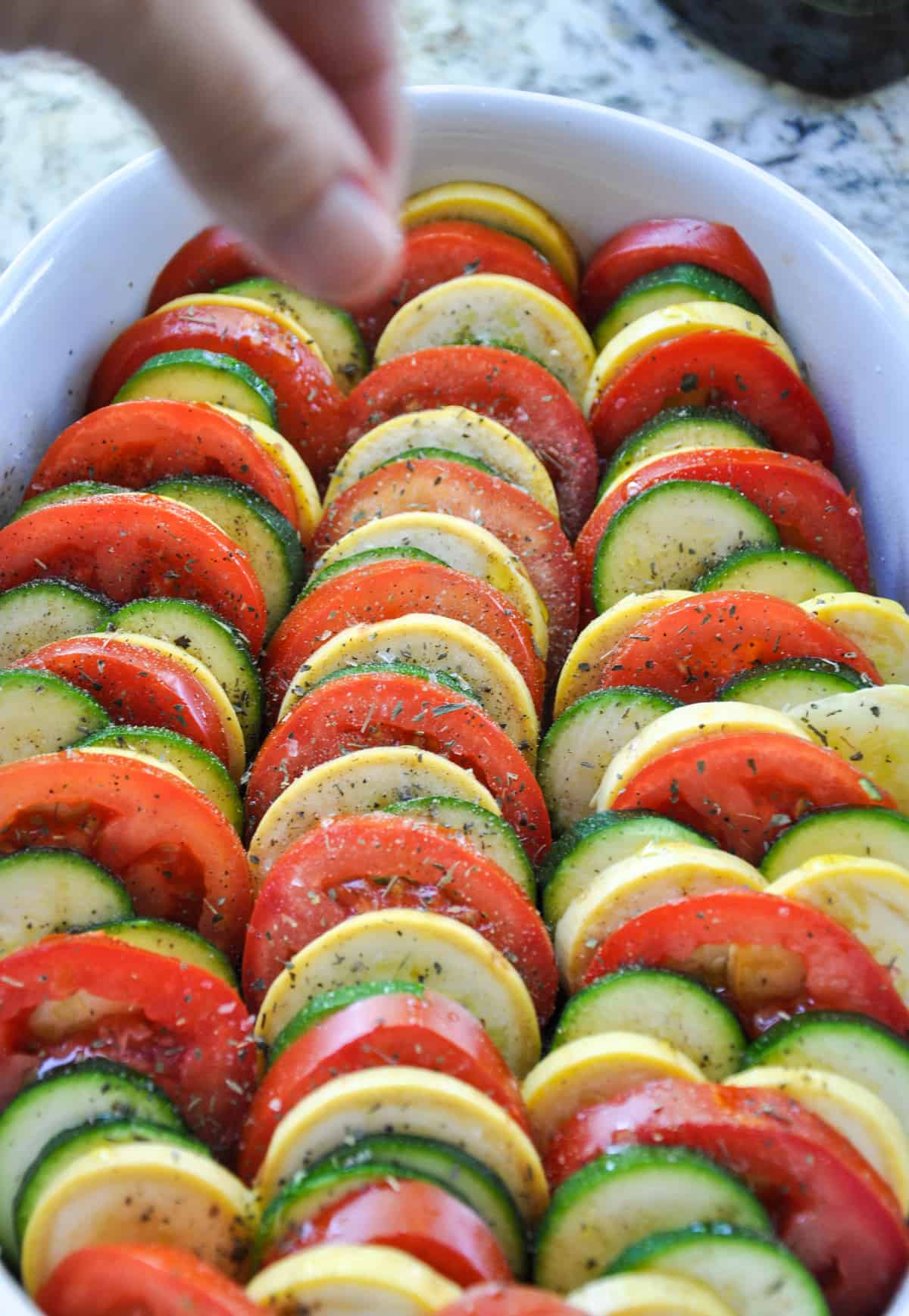 Sprinkle dried basil over layered zucchini and tomatoes
