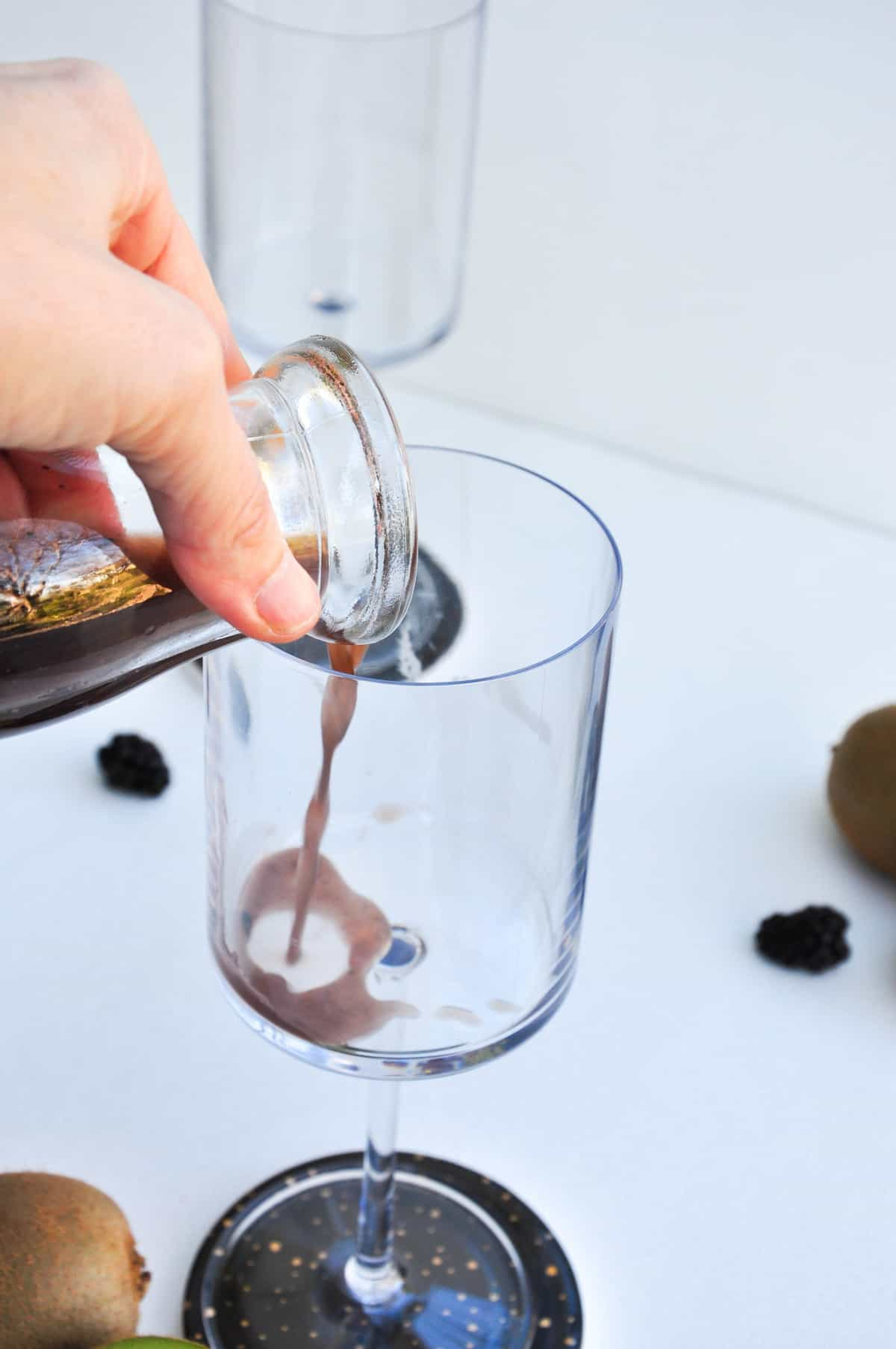 Pour kiwi juice and blackberry juice into champagne glass