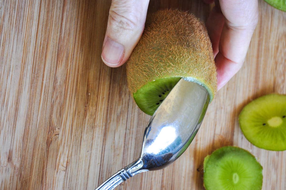 Remove the kiwi skin with a spoon, circling the kiwi fruit