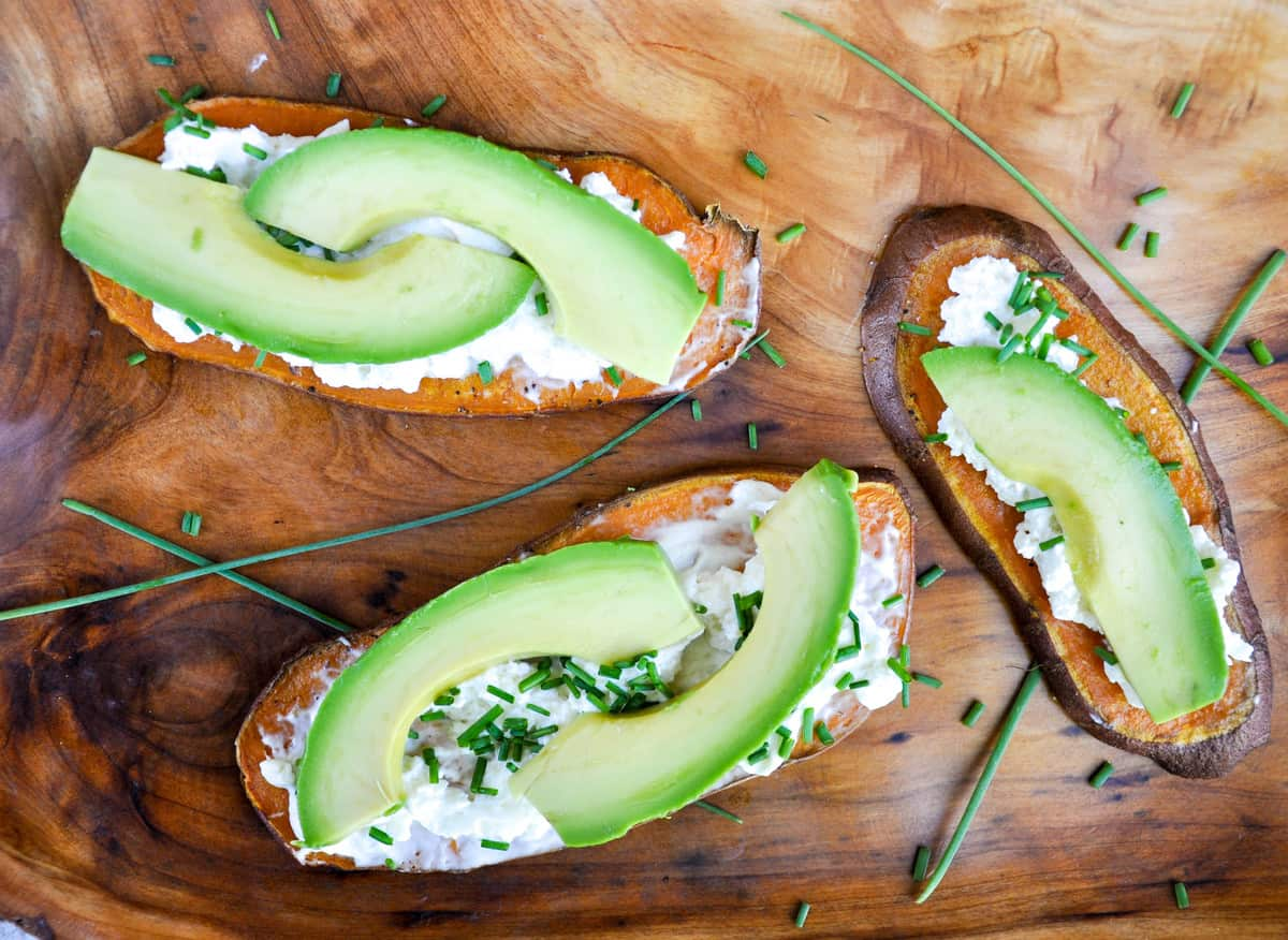 Sweetptoatoes topped with cream cheese, avocado, and chives