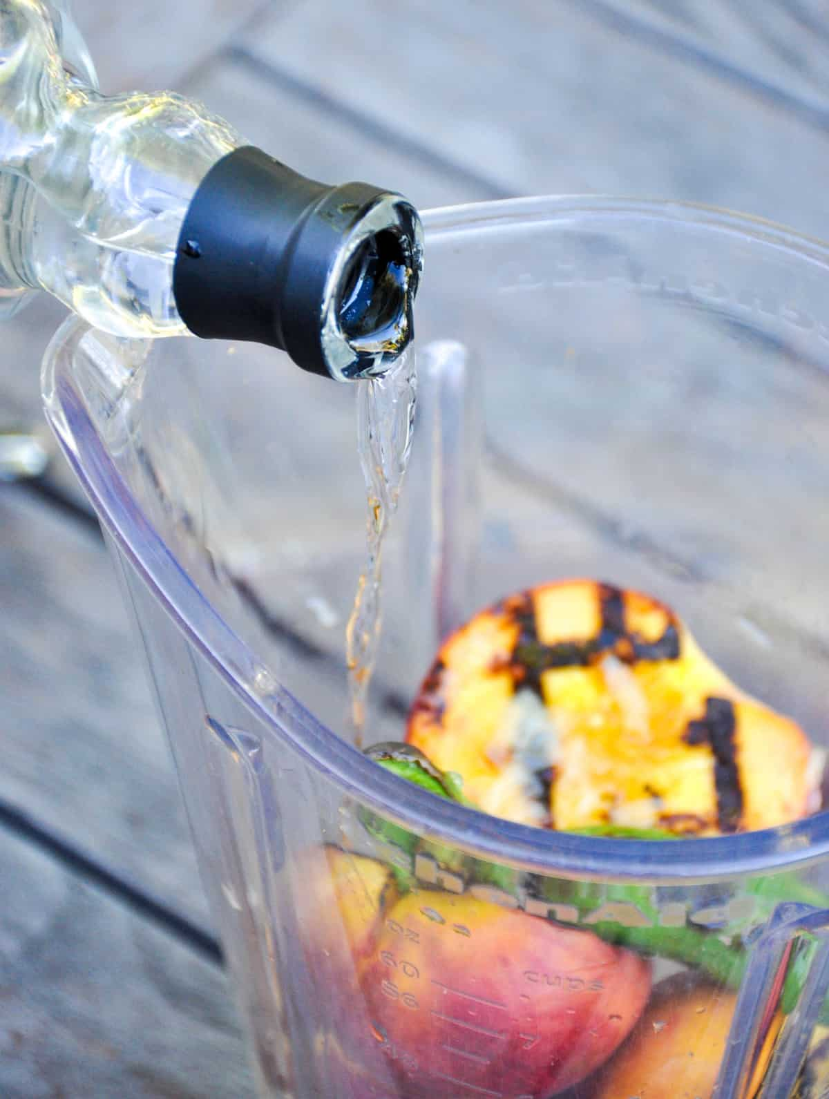 Pour tequila in blender over grilled peach and jalapeño