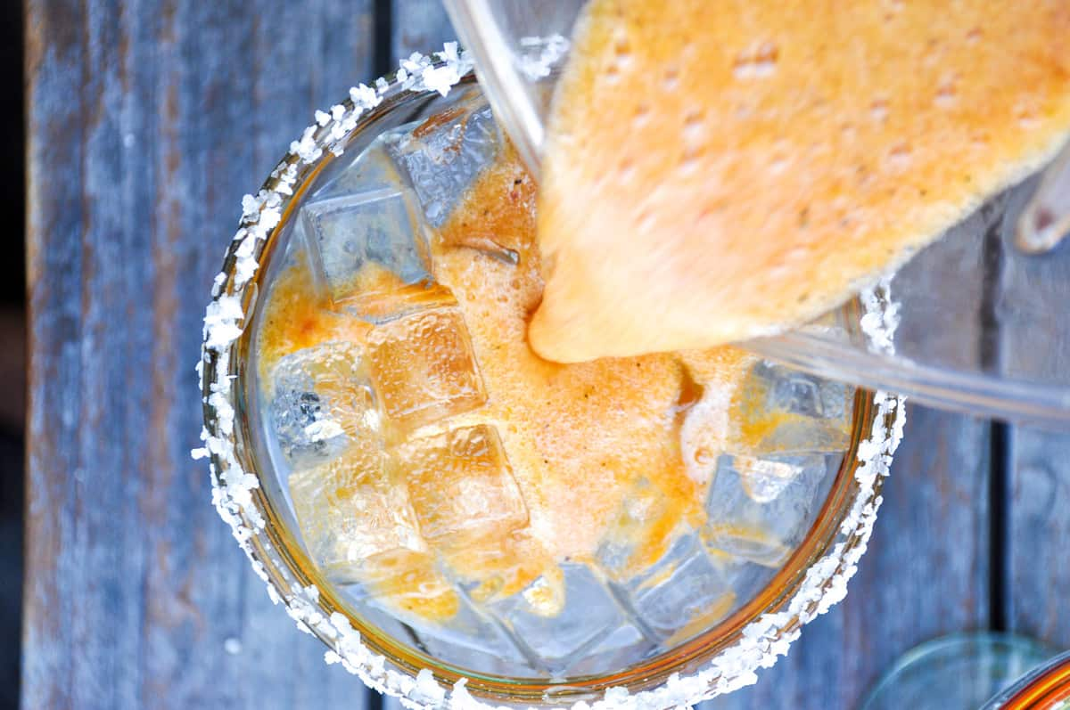Pour blended spicy grilled peach margarita over ice