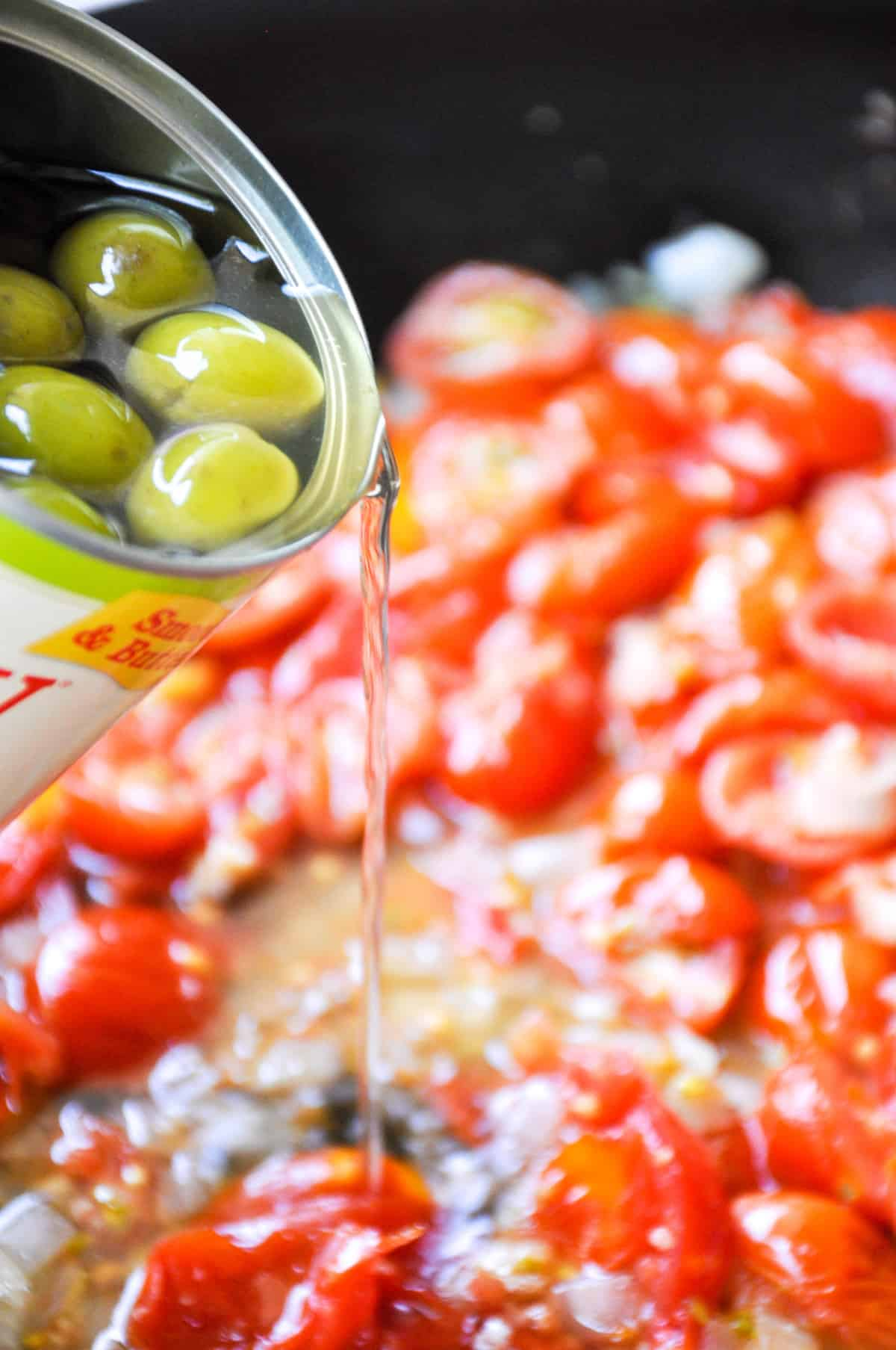 Add water from green olives can to cooked down tomatoes