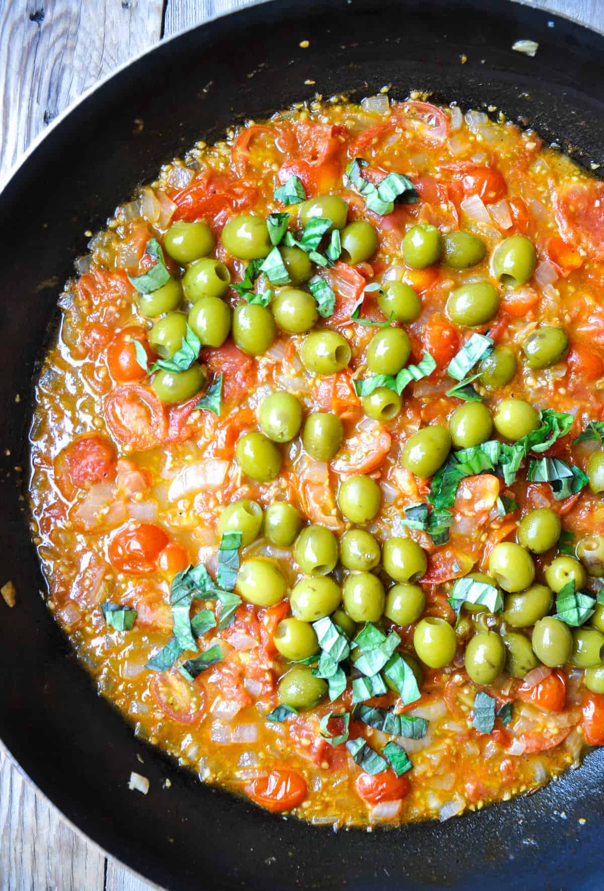Add in green olives and fresh, chopped basil
