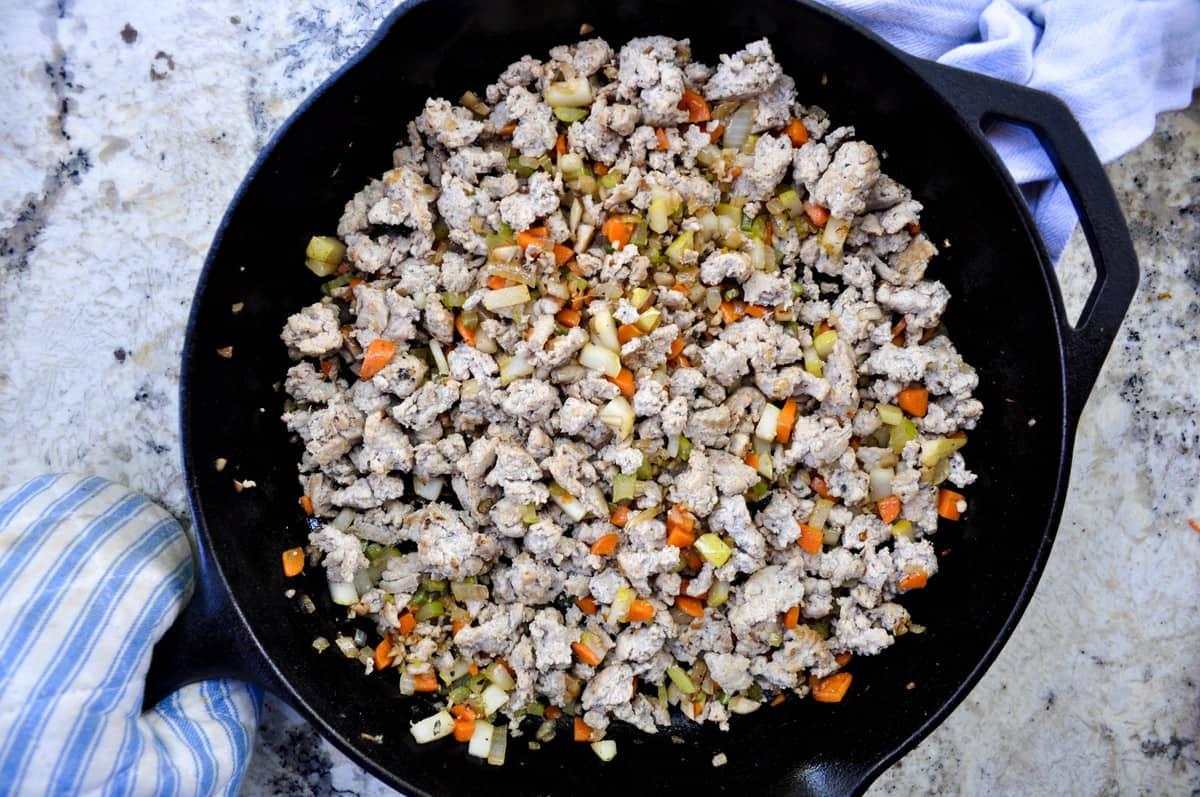Ground turkey, onion, carrot, celery, mushroom and Bartlett pear in skillet