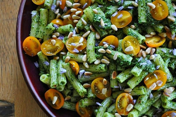 A vibrant green pasta with yellow cherry tomatoes, pine nuts, and herbs.