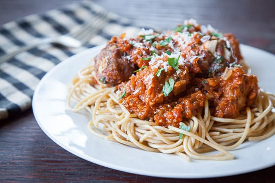 A plate of Spaghetti and Meatballs with Roasted Tomato Sauce . This classic tomato recipe is topped with Parmesan cheese and basil.
