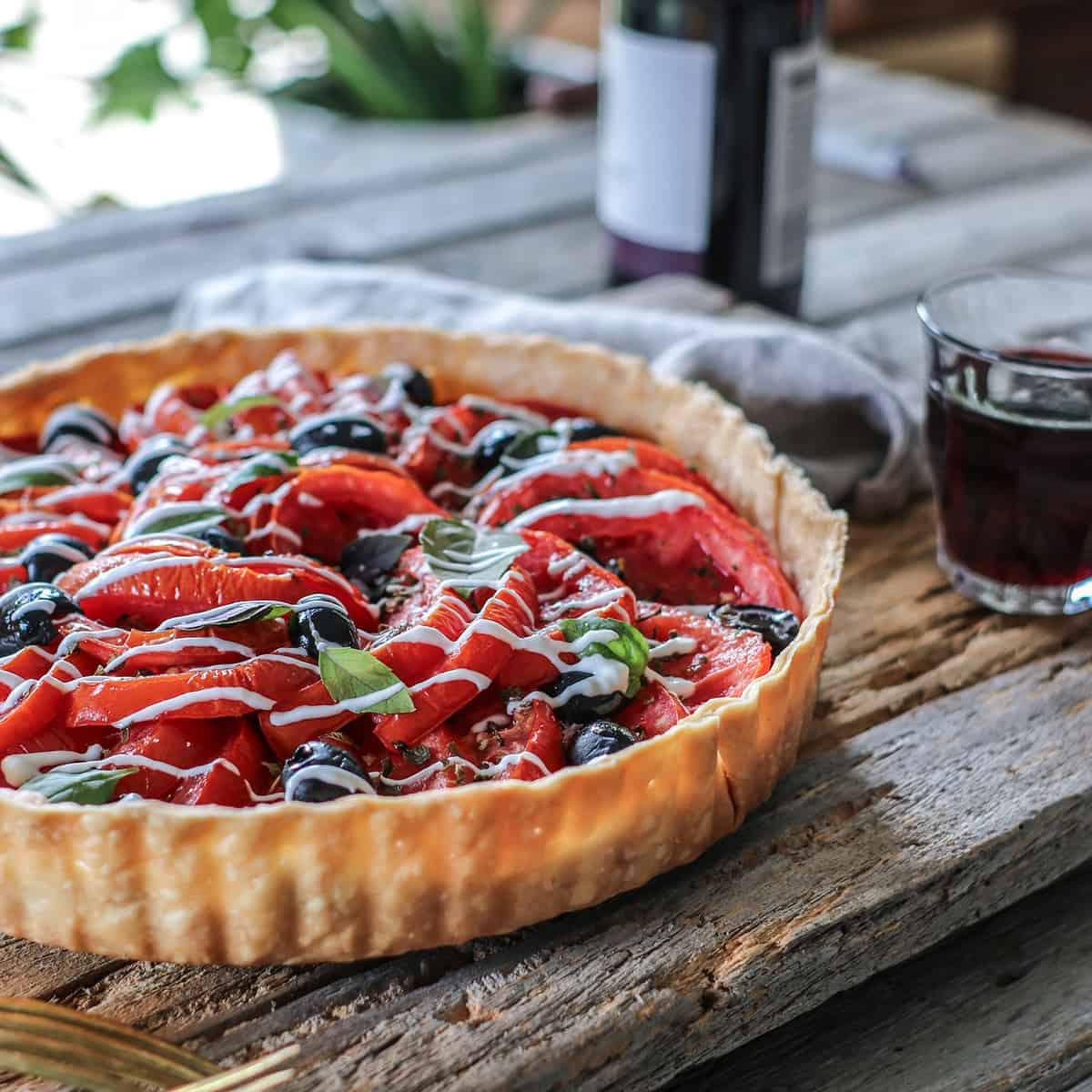 Heirloom Tomato and Black Olive Tart on a serving table next to a glass of red wine.