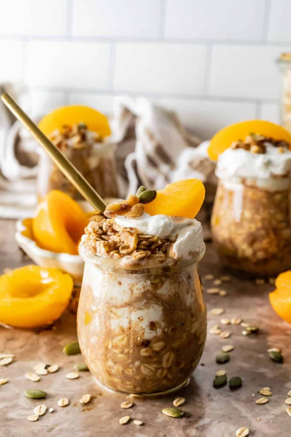 This recipe with canned peaches is for Peach Cobbler Overnight Oats. Glass jars are filled with overnight oats and topped with peach slices and yogurt .