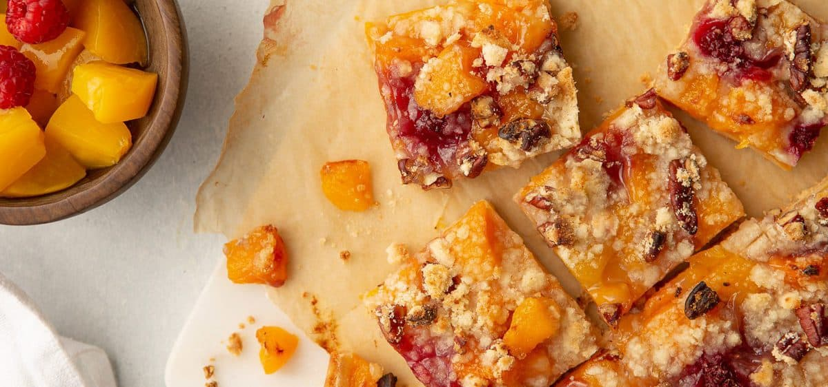 This recipes with canned peaches also calls for raspberries all baked over a shortbread crust then sliced into squares to serve.
