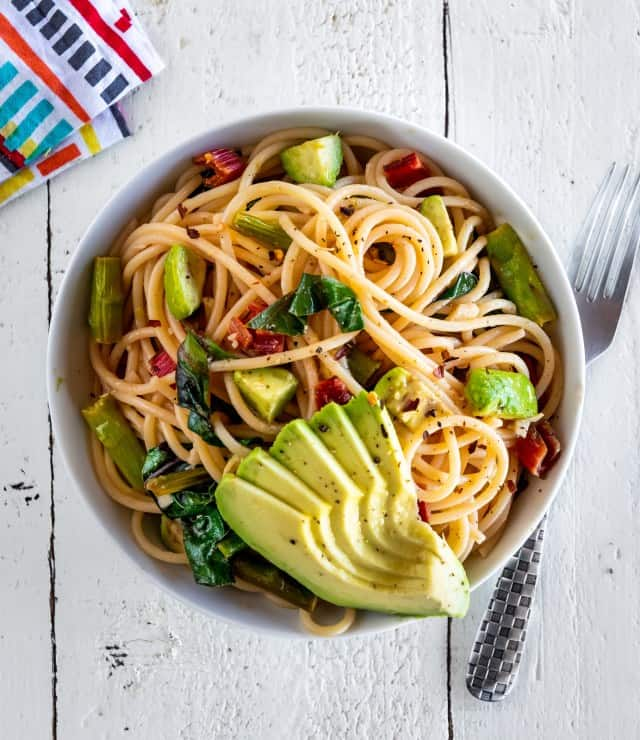 A bowl of Spaghetti with Asparagus, Wilted Greens, and Avocado. This recipe sauces the asparagus which is one of the best ways to cook asparagus.