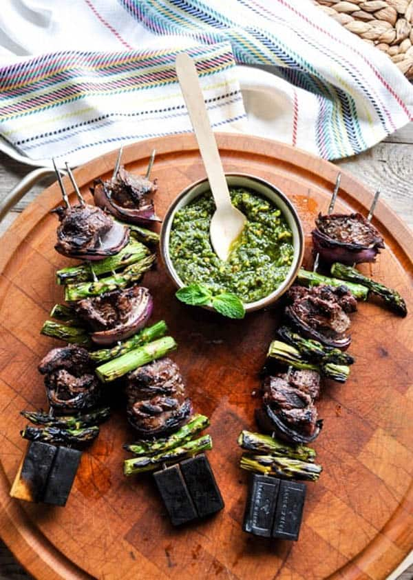 3 grilled lamb asparagus and red onion kabobs on a wooden platter with a bowl of pistachio mint pesto.