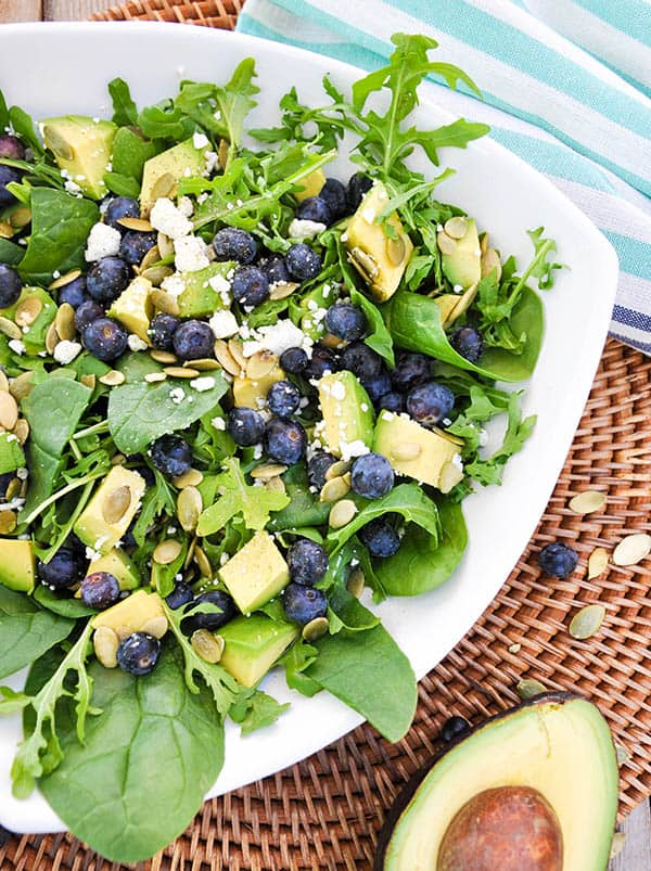 A platter of Blueberry Avocado Salad. Fresh blueberries and avocado are on top of arugula and mixed greens. Feta and pumpkin seeds are scattered over the top of the salad.
