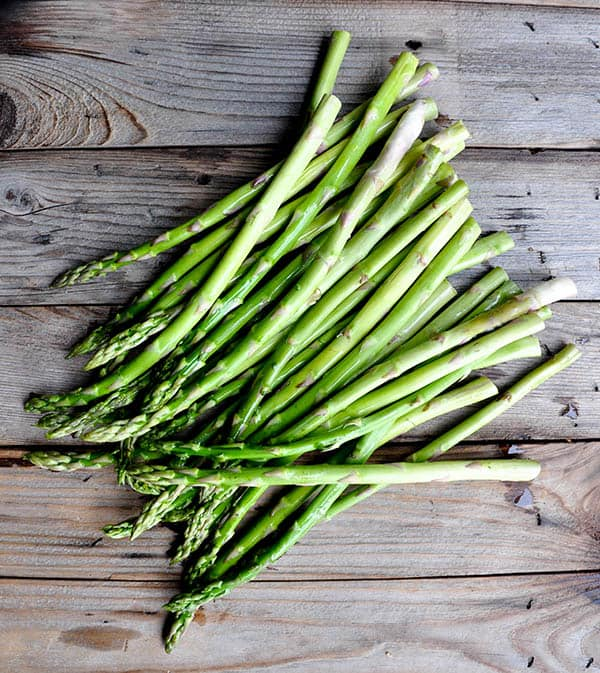 Fresh asparagus spears lying on wood background.