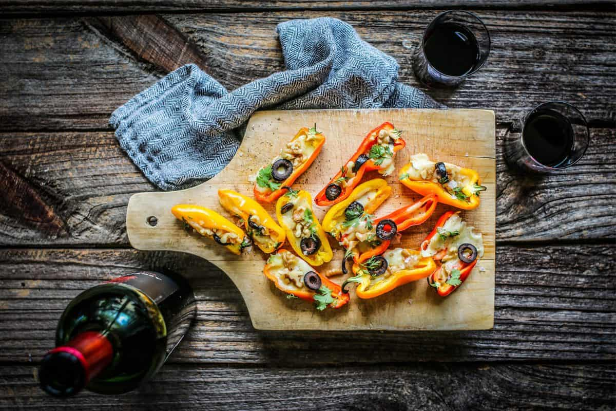 Mini Stuffed Peppers Recipe with Olives and Pepper Jack Cheese on a wooden serving board with a glass of red wine