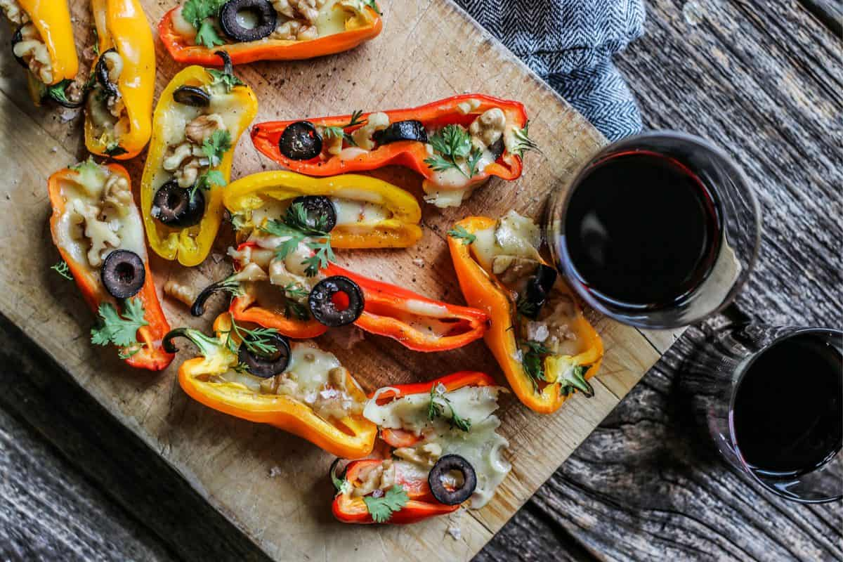 Mini Colorful Stuffed Peppers Recipe with Olives and Pepper Jack Cheese on a serving board with a stemless glass of red wine.