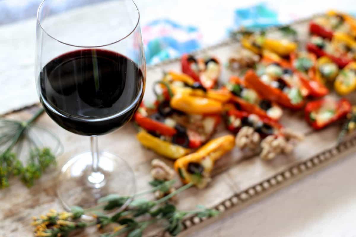 Mini Stuffed Peppers Recipe with Olives and Pepper Jack Cheese on a wooden serving board in the background. A glass of red wine is next to the serving board.