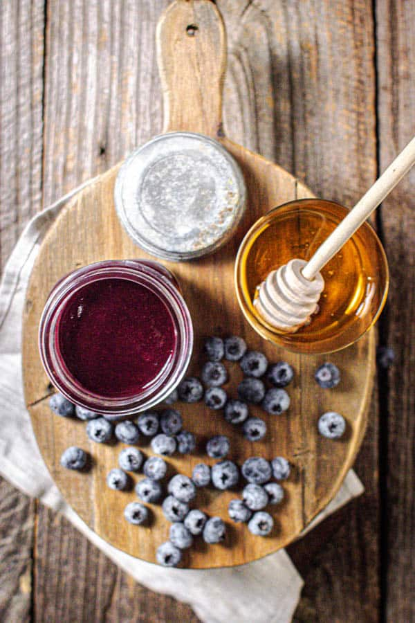 A jar of homemade Blueberry Jalapeño BBQ sauce is on a wooden board next to a jar of honey and fresh blueberries.