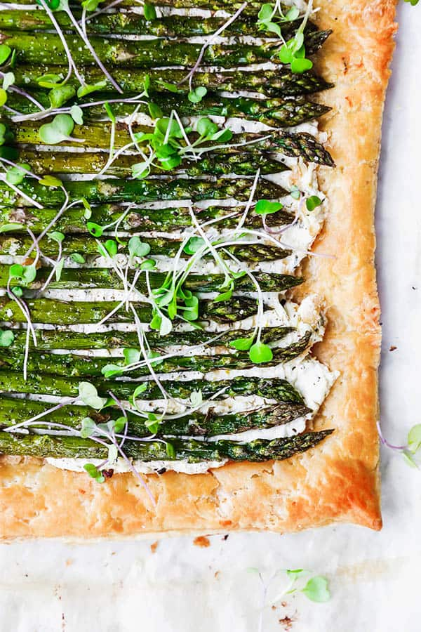 A Roasted Asparagus and Goat Cheese Tart topped with a sprinkle of micro greens. Roasting is one of the best ways to cook asparagus.