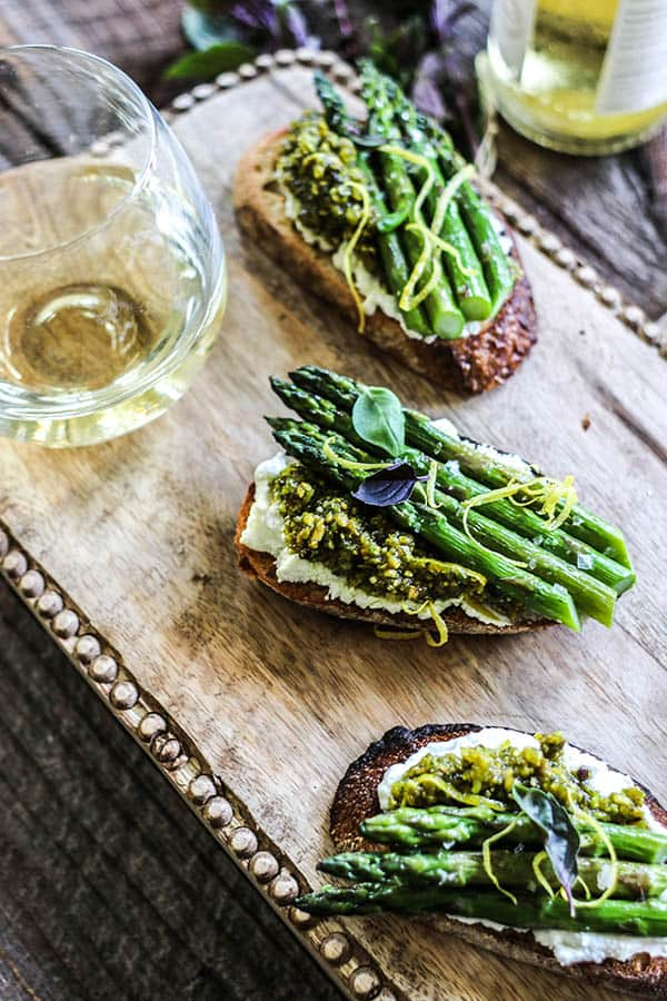 3 bruschetta with Warm Goat Cheese, Roasted Asparagus, and Pistachio Pesto on a wooden serving board next to a glass of white wine.