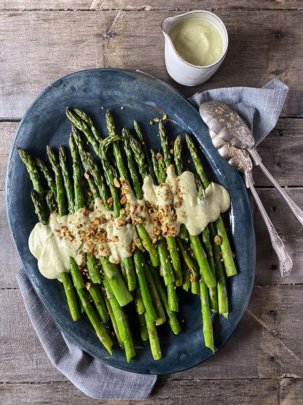A platter of roasted asparagus topped with a garlic, tahini, and avocado dressing then sprinkled with crushed pistachios