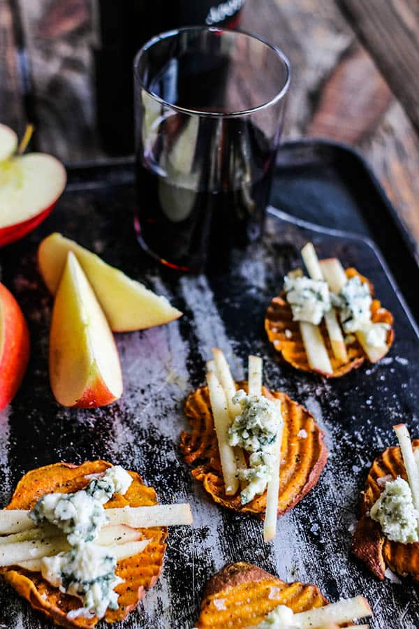 California Sweet Potato Rounds with crumbled blue cheese and matchstick apple slices on top paired with a glass of red wine.