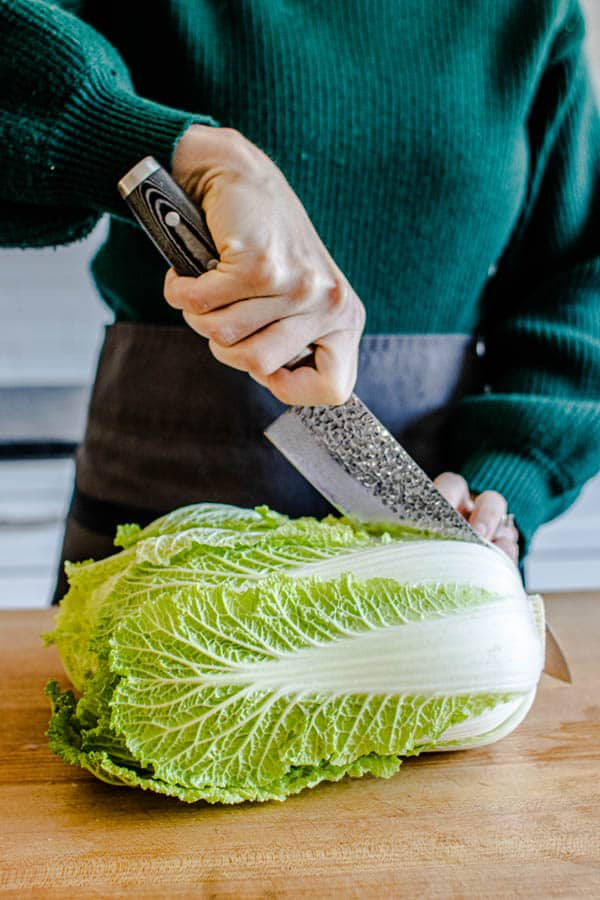 Breaking down a head of Napa cabbage by slicing it in half through the core towards the ends of teh leaves for our Melting Napa Cabbage recipe.