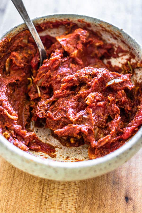 A bowl of tomato paste mixed with sliced garlic and spices for Melting Napa Cabbage.