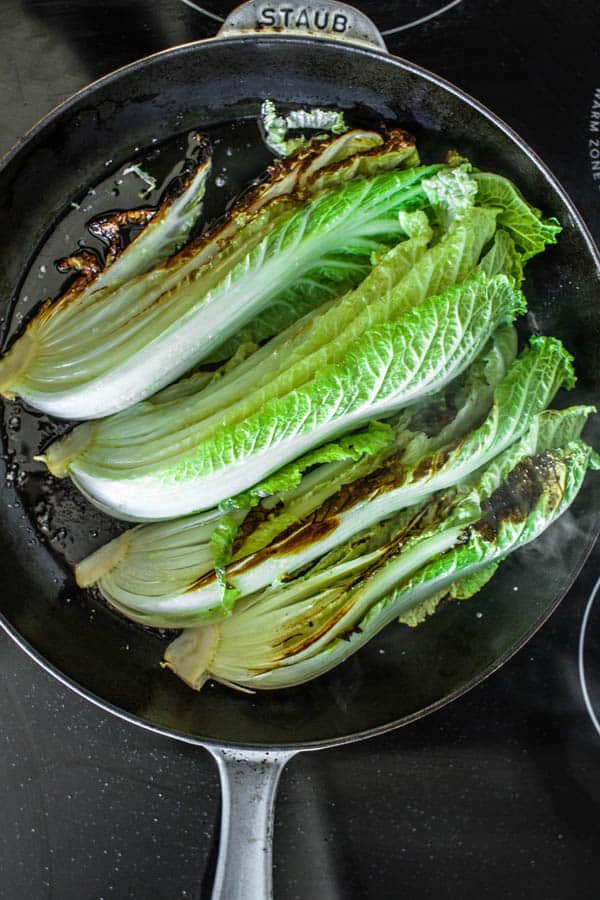 Napa cabbage wedges being seared in a cast iron skillet for Melting Napa Cabbage recipe