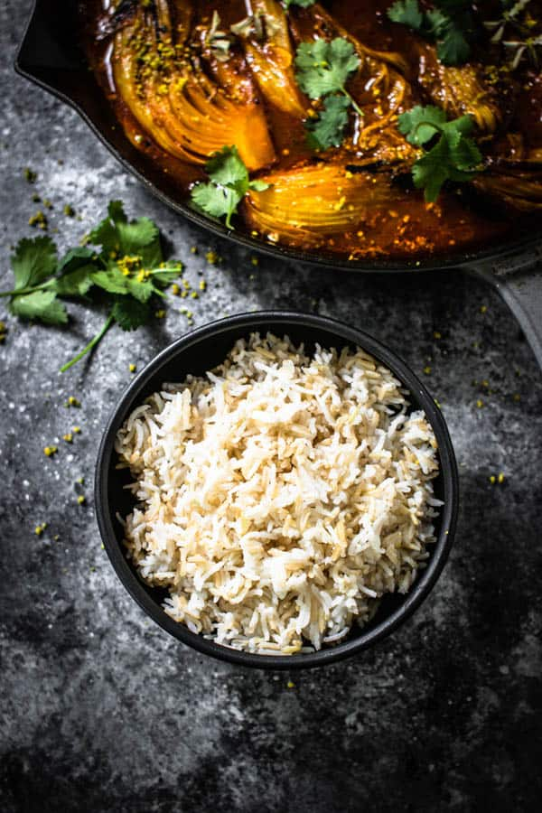 A bowl of 50/50 rice - half white rice, half brown rice next to a skillet of Melting Napa cabbage ready to be served.