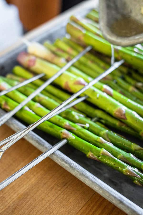 "Leftover olive pil and lemon juice seasoning being poured over asparagus ""rafts"" before they are grilled."