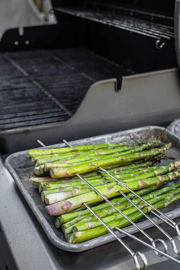 Prepared asparagus sitting next to the grill as it preheats