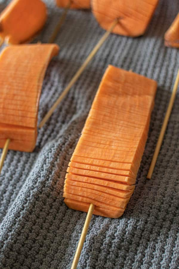 Hasselback Sweet Potato Skewers drying after soaking on kitchen towel.