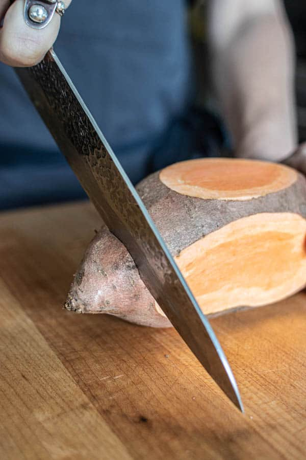 A sweet potato that has had the sides slightly shaved down to create flat edges and teh ends are being cut off creating a rectangle.