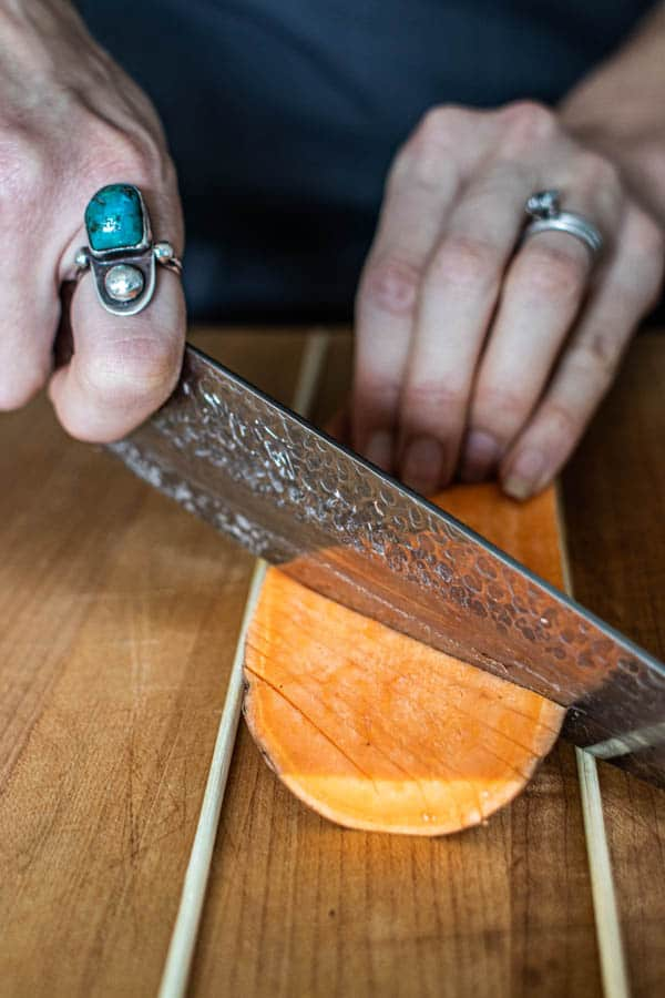 Horizontal cuts being made in a sweet potato slab for Hasselback Sweet Potato Skewers.