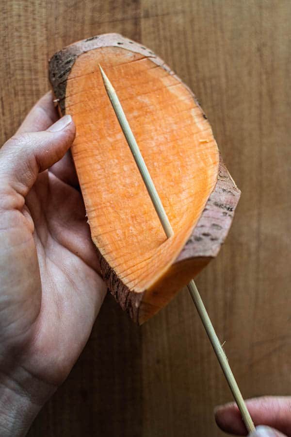 A slab of sweet potato that has been sliced vertically and horizontally to create an accordion pattern is being threaded onto a wooden skewer.