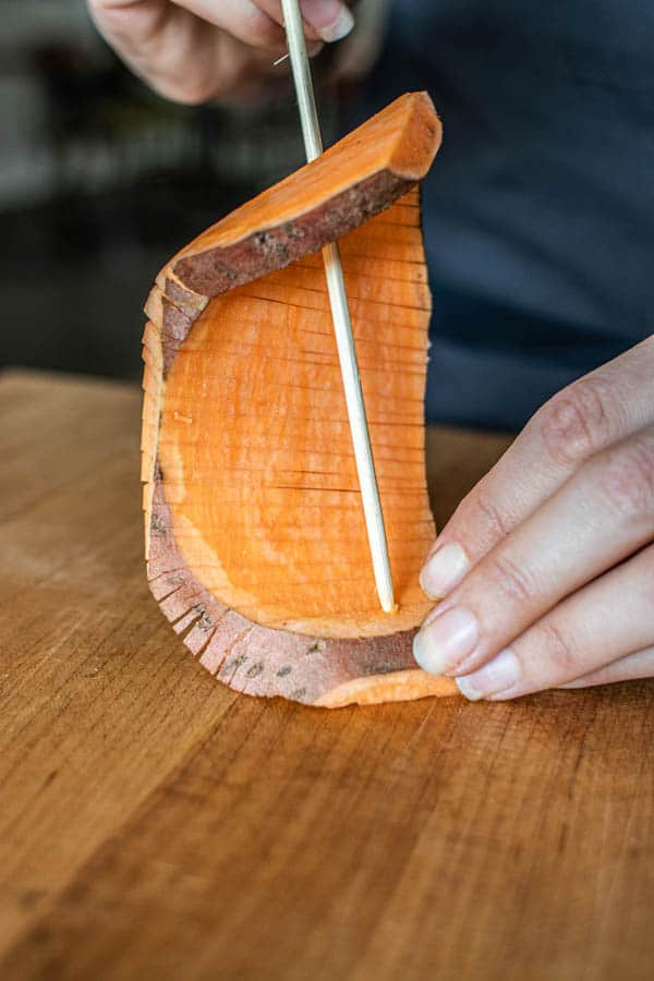 A Hasselback sweet potato slab being threaded onto a skewer.