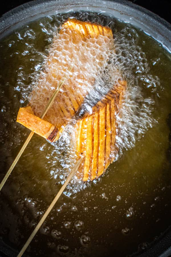 Hasselback Sweet Potato Skewers cooking in hot oil.