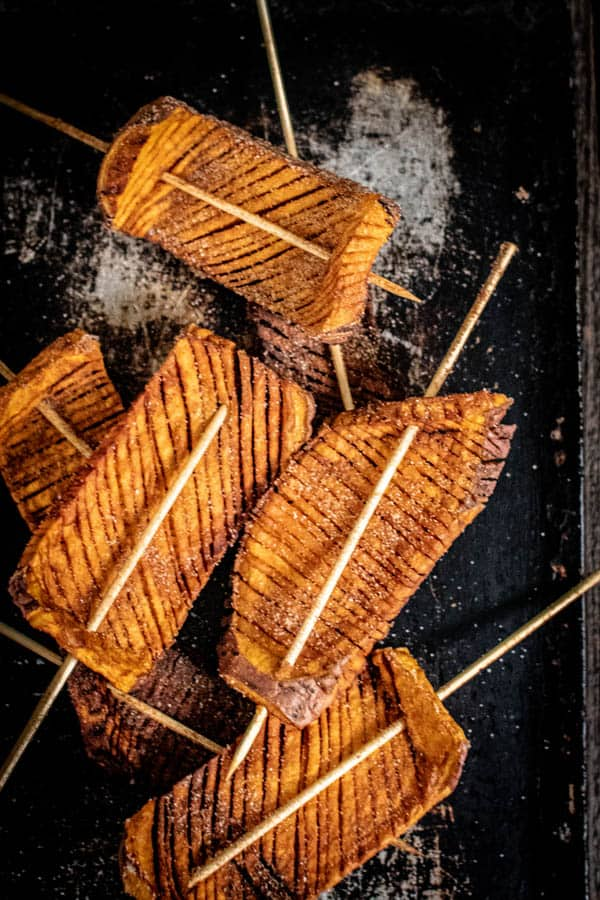 Thick slabs of sweet potato  that have been intricately cut to achieve an accordion effect then threaded onto skewers. The 5 Hasselback Sweet Potato Skewers are on a black serving tray.