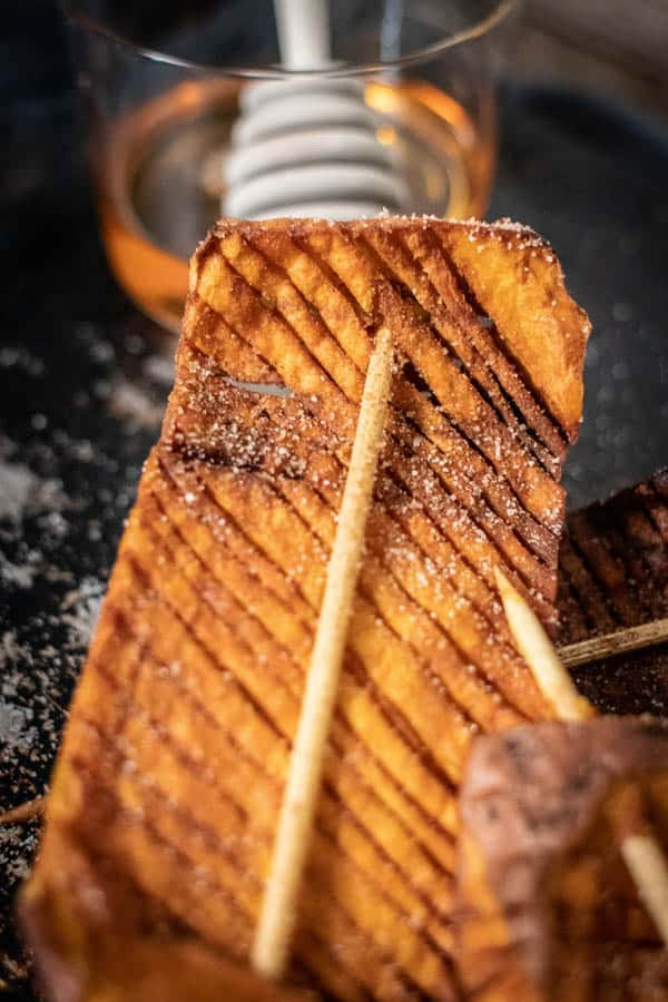 A close up image of a Hasselback Sweet Potato Skewer dusted with cinnamon and sugar.